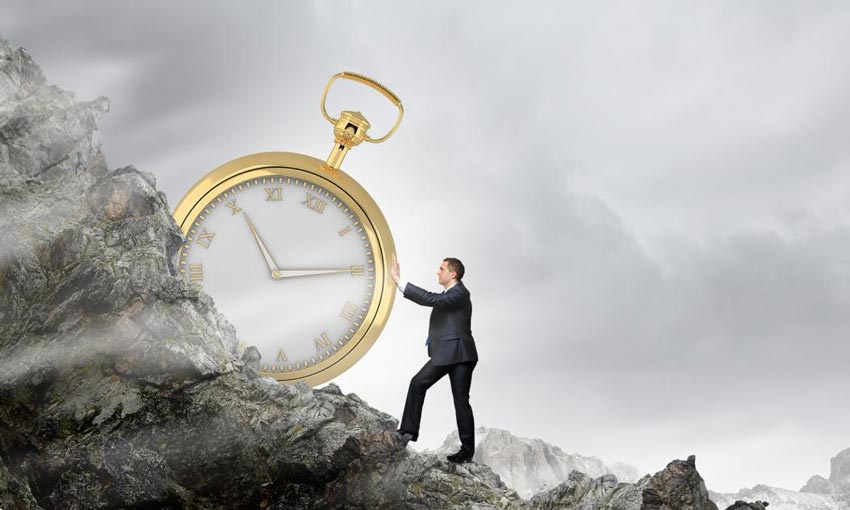A man pushing a clock up a hill